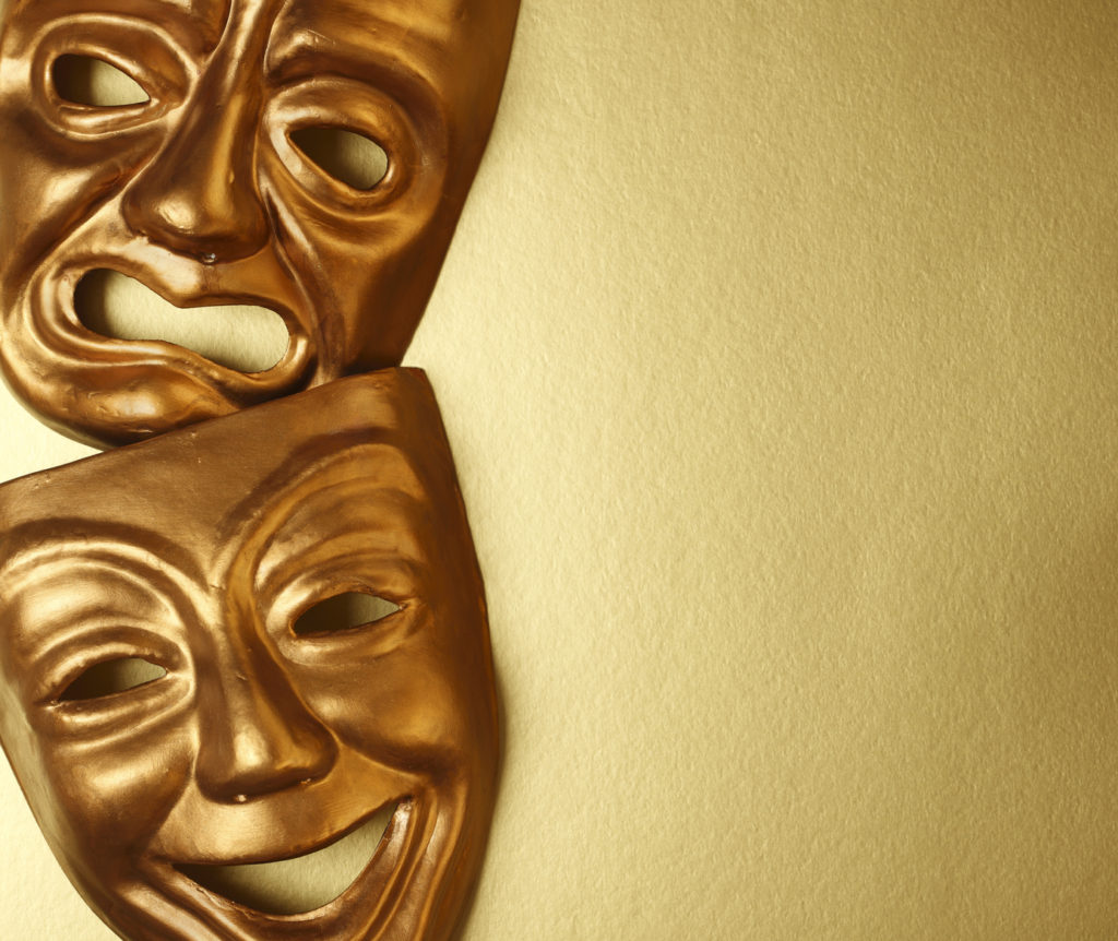 Classic gold comedy-tragedy theater masks with copy space.